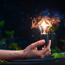 Lightbulb with a butterfly inside in a hand. Merging science and magic creative still life concept with copy space.